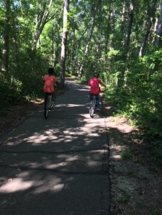 Two of the kids leading the biking group on a woodsy paved path.