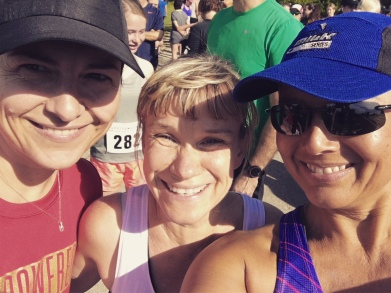 Image description: Left to right Violetta (black cap, red t-shirt, fine chain with pendant), Ellen (blond hair tied back, bangs, white tank), and Tracy (blue cap and sunglasses, purple and pink tank), all smiling.