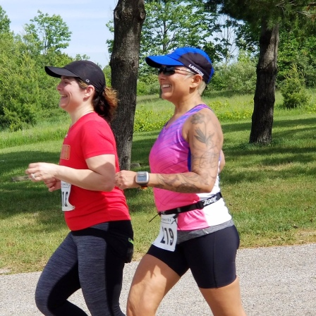 Image description: Tracy and Violetta running side by side, smiling, trees in the background.