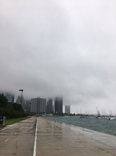 Image description: rainy day with low mist, tall buildings in background, concrete lakeside path with painted lines, lake on the right with sailboats on moorings.