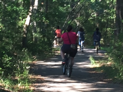 Me riding behind the kids on a paved woodsy path.