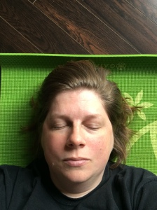 The author, a white woman in her mid-forties, with light brown hair, wearing a black shirt, lies on a green mat. Her eyes are closed.