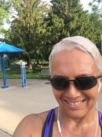Image description: Headshot of Tracy in foreground, short hair, sunglasses, earbuds, smiling. Background is trees, partial view of park bench, distance marker and pavement.