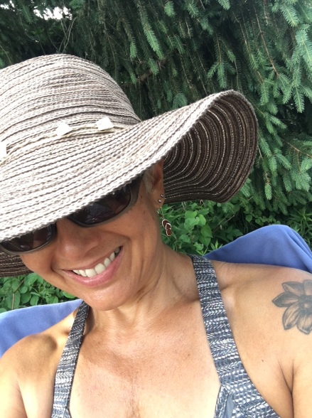 image description: Tracy at the campground in a wide-brimmed sunhat, sunglasses, and an 'active dress,' smiling, pine tree in background.