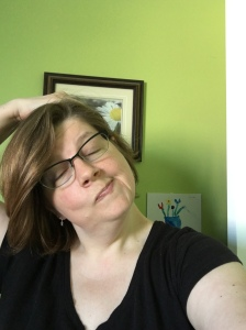 The author, a white woman with light brown hair and glasses and wearing a black shirt, is using her right hand to gently pull her head to the right and stretch the left side of her neck. Her eyes are closed and she is smirking.