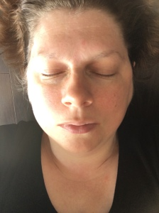 The author, a white woman in her mid-forties with short brown hair is lying on a brown wooden floor. Her eyes are closed.