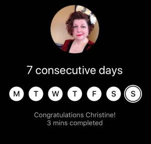 A screen capture from the Insight Timer app, the author, a white woman in her forties, is pictured in a small round image, she has her short brown hair pulled back on one side, she is smirking and she is wearing red lipstick. Beneath her photo are 7 white circles representing the days of the week. Text below reads 'Congratulations, Christine. 3 mins completed.""
