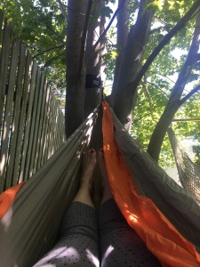 The photo depicts a pair of legs in a hammock. The person is wearing grey capris that have black polka dots on them. The hammock is grey and orange and is hanging from a large tree, there is an unpainted fence to the left.