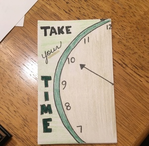 A rectangular index card rests on a wooden surface. The card has a drawing of one side of an analog clock face, which is outlined in green, and the words 'Take your time' are written on the left side of the card.