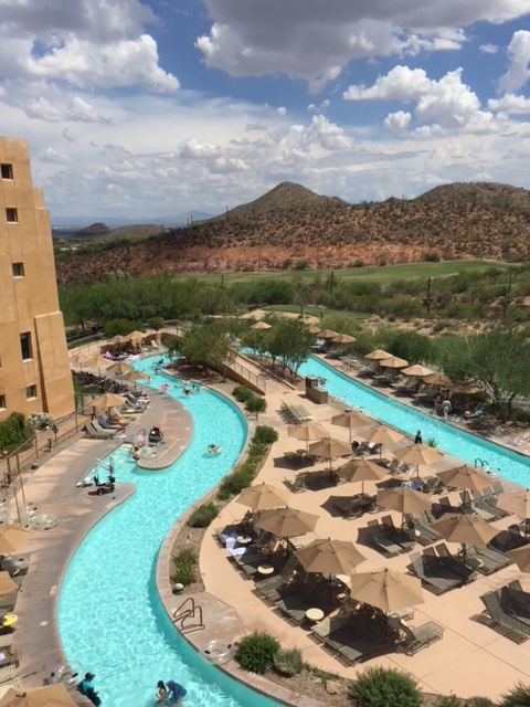 A lazy river pool at a desert hotel, with trees and desert mountains in the background.
