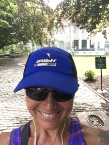 Image description: head shot of Tracy, smiling, blue ball cap and sunglasses, one of the Newport Mansions in the background.