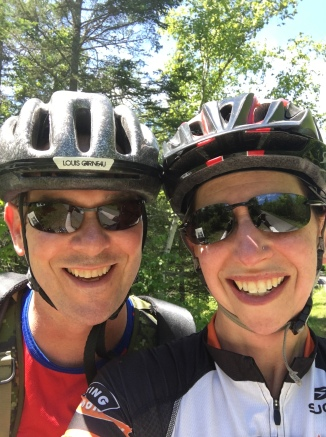 Two happy people in bike helmets and sunglasses. Seriously happy people.