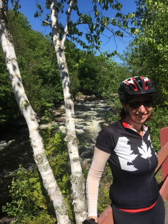 Rivière Du Nord in the background and a birch tree with a smiling bicyclist wearing a maple leaf shirt in the foreground.