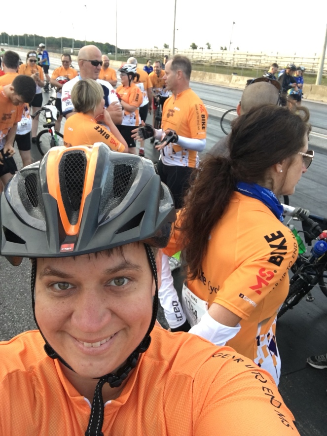 Natalie faces the camera smiling. Behind her is a group of people chatting animatedly wearing orange cycling jerseys
