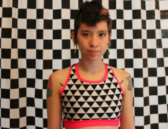 A geomtric black and white tank style swim top with pink edging.