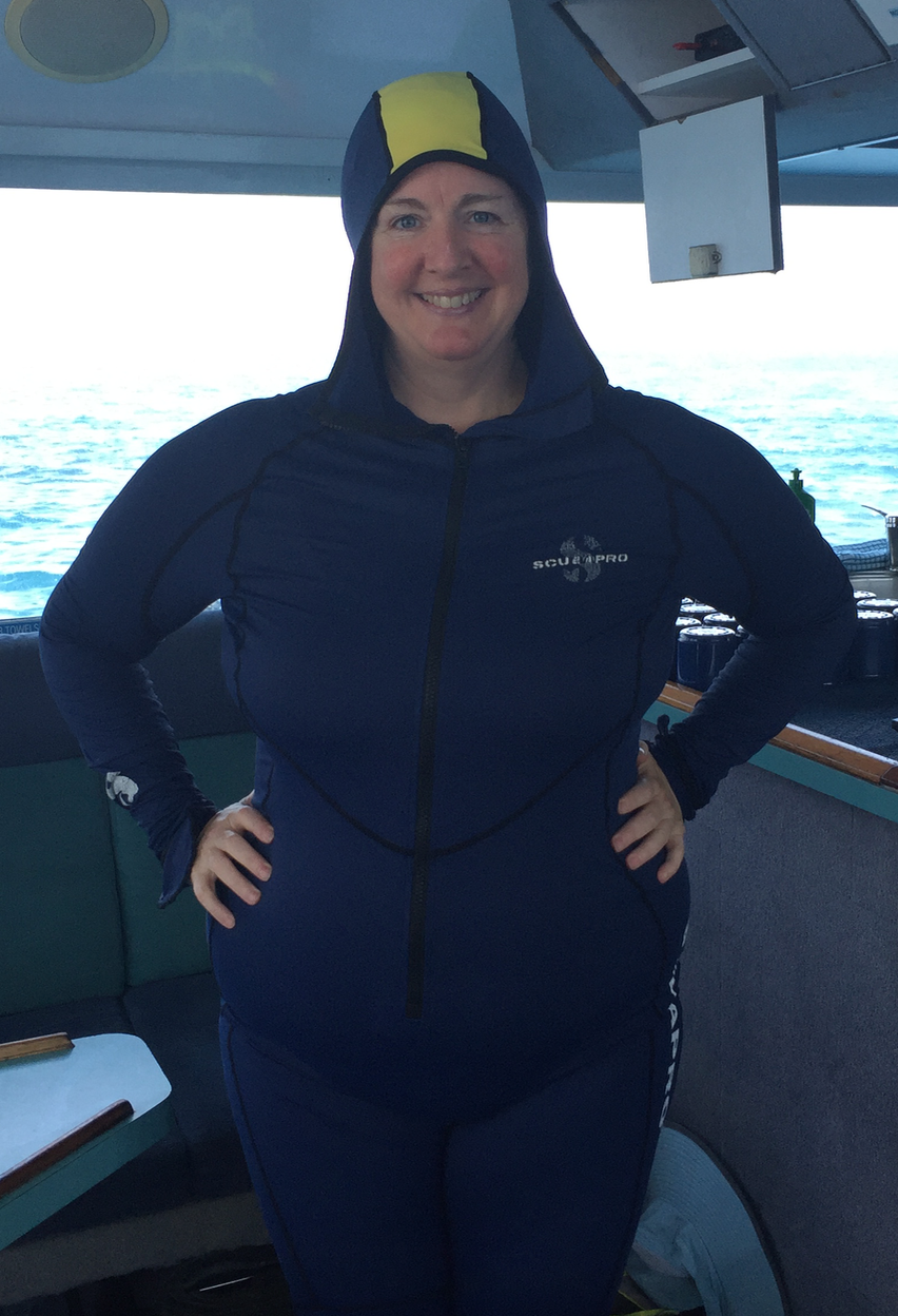 Me in a blue stinger suit with a blue and yellow hood, before scuba diving.