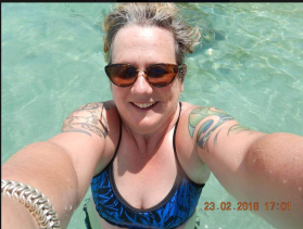 Samantha selfie with blue patterned thin strappy top, and tattooed shoulders, in clear aquamarine water.