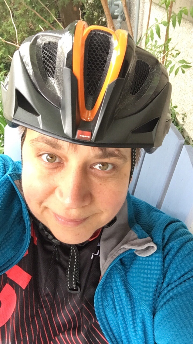 Nat takes a selfie in her bike helmet smiling.