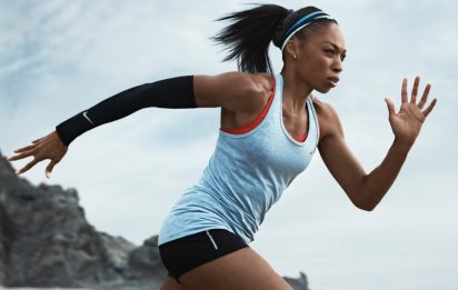 Image description: Upper body shot of strong woman running in a tank top, shorts, a black arm warmer on her right arm, hair in pony tail and a headband. Sky and rocky hill in background.