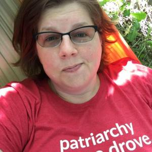 The author, a white woman with light brown hair and glasses, is lying in an orange and grey hammock. There is a small patch of green plants in the upper right of the photo. She has a tired smirk and she is wearing a red tshirt that reads 'patriarchy got me drove.'