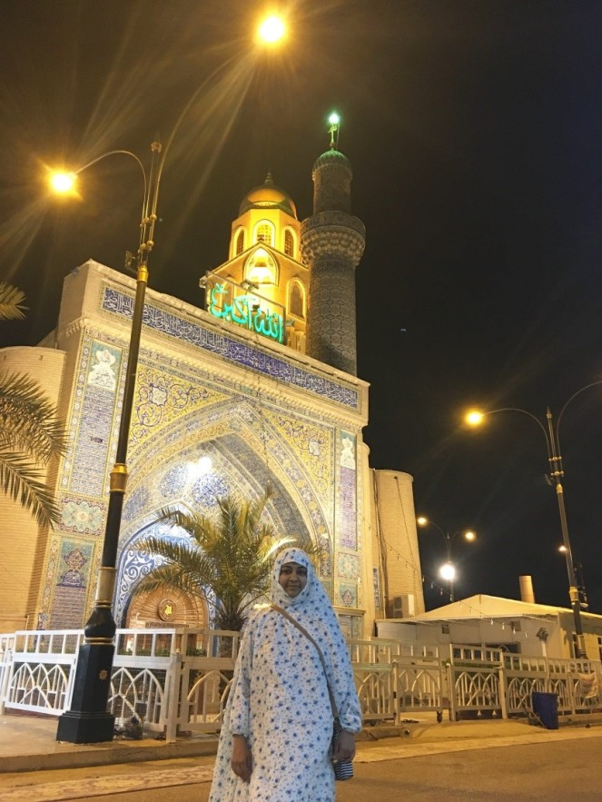 a brown woman standing in front of the entrance of a large mosque at night time.
