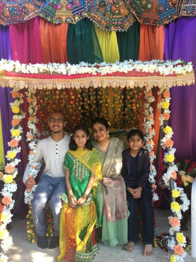 A man, a woman, and two kids sitting on a flower-decorated swing