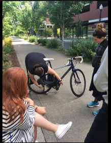 Me leaning over a road bike, bending the rear derailleur and replacing the chain, while others look on.