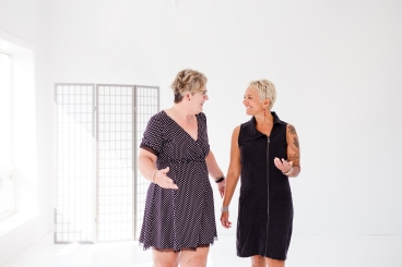 Image description: Sam in a black and white polka dot dress, short hair with highlights, on left, looking at Tracy in a black dress with a zipper, short cropped hair, on right. They are chatting to each other, making hand gestures and smiling, against a plain white back drop.