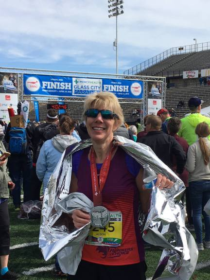 Image description: Alison (short blond hair, sunglasses) at the finish line of the Toledo Marathon, foil blanket over shoulders, medal around neck, sunglasses, smiling. People and finishing arch in background. Partly cloudy skies.