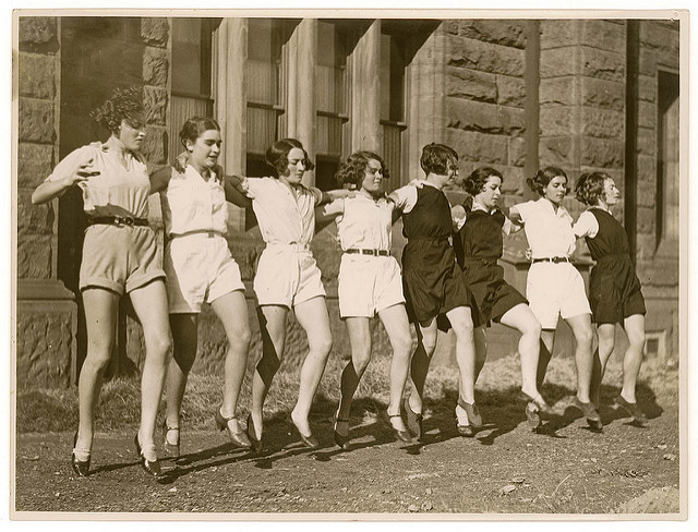 black and white 1930's era eight women about 15 years old lined up arms linked likely mid can-can style dancing