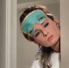 Actress Audrey Hepburn as Holly Golightly in Breakfast at Tiffany's. She is a slender, brown-haired woman and she looking out around her apartment door. Only her head and one shoulder can be seen, she is wearing a light blue sleep mask pushed up on her forehead and there is a tassel visible, dangling from her right ear.