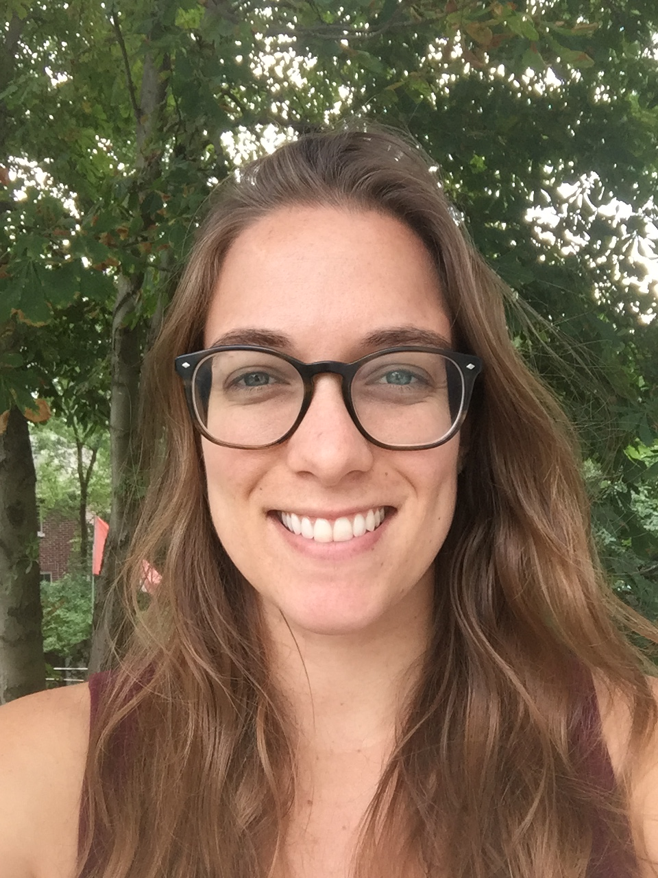 Image description: Head shot of Cami, a young white woman with glasses and long brown hair, smiling, trees in the background.