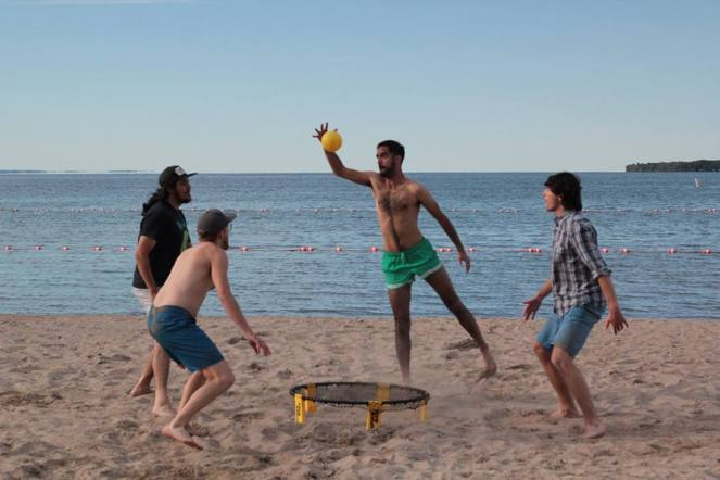 Image description: Four men wearing shorts and some wearing shirts are evenly spaced around a small black, circular netting with yellow posts. One man in green swim trunks is extended in the air with this hand contacting a small yellow ball. Beach scene with a lake in the background.