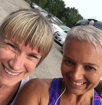 Image description: Ellen and Tracy selfie after MEC 10K. Ellen on left, blond hair with straight bangs, smiling, white tank; Tracy on right, smiling, short blond hair, sunglasses atop head, smiling, pink and purple tank, white earbuds cord hanging around her neck; trees and parked cars in background.
