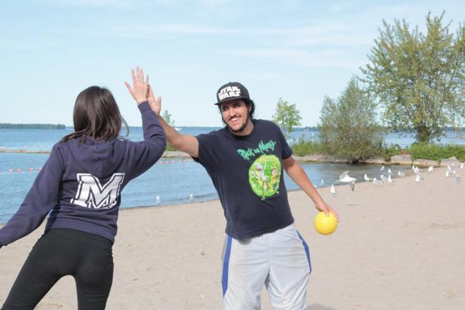 Image description: Man in a hat, t-shirt and shorts holding a yellow ball reaching out and high-fiving a woman wearing a blue hoodie and black pants. Beach scene with seagulls in the background.