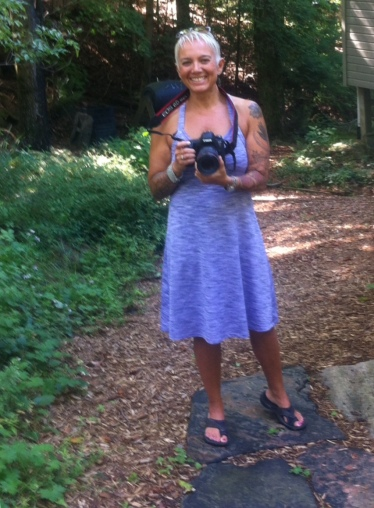 Image description: Tracy standing on a rock slab, smiling, short blond hair, violet dress sandals, holding a camera, strap around her neck, bark mulch and trees behind her. Photo credit: Irene Steinhardt