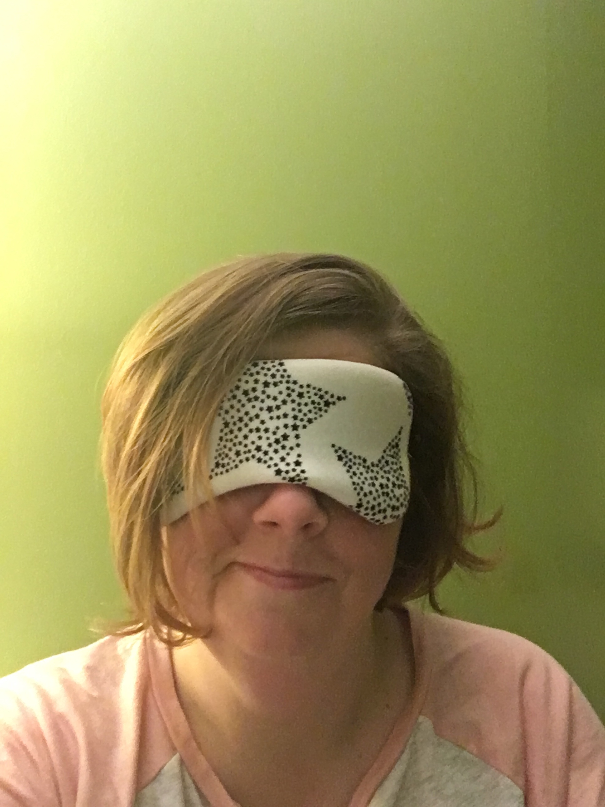 The author, a white woman in her 40s with chin-length brown hair, is wearing pink and white pyjamas and  a white sleep mask that has black stars on it. She is smirking. The background of the photo is green.