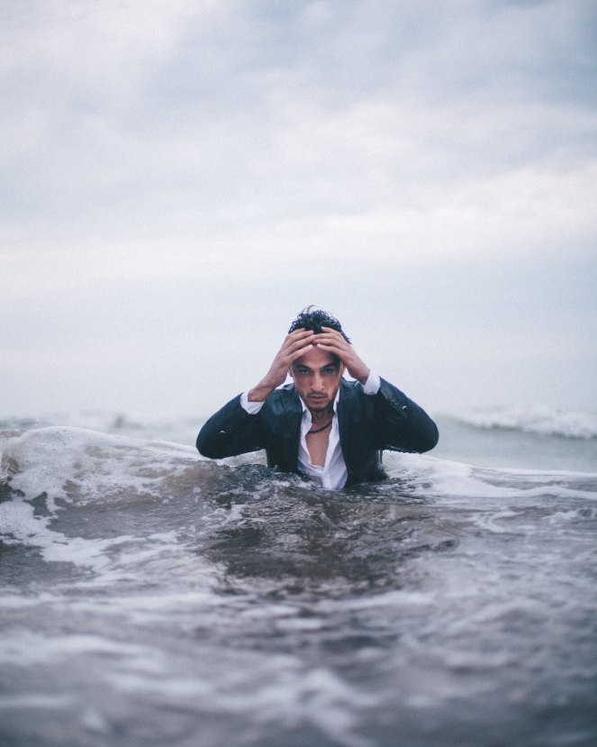 Blue sky, grey water. A man wearing a suit up to his chest in water. He's got a very worried face and he's running his hands through his hair.