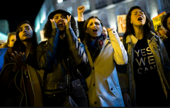 Women at a protest march, mouths open, shouting or singing or chanting.