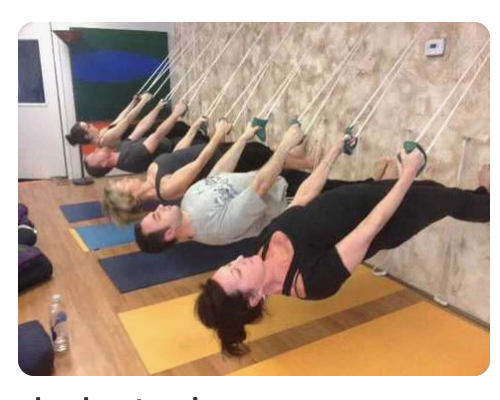 A whole bunch of people with their feet on a wall, extending parallel to the floor, holding ropes to keep them in place.