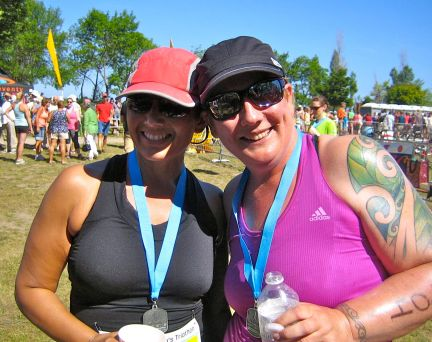 Image description: Tracy on the right Sam on the left, both smiling, wearing caps and sunglasses, medals around neck, people, trees, and sky in the background, after the Kincardine Women's Triathlon in 2013, when they weren't quite yet 49.