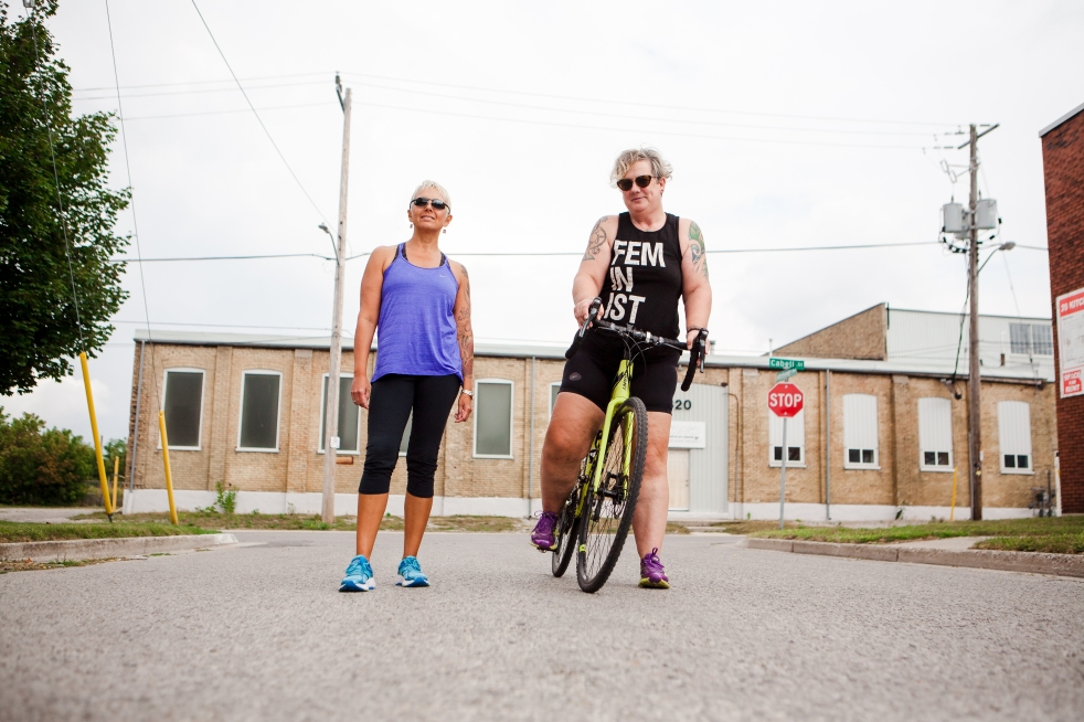 Image description: Low angle urban street shot of Tracy, standing in workout clothing, Sam, in workout clothes with a black tank top that says FEMINIST, on her bike, standing with one foot in the pedal. Stop sign and building in background.