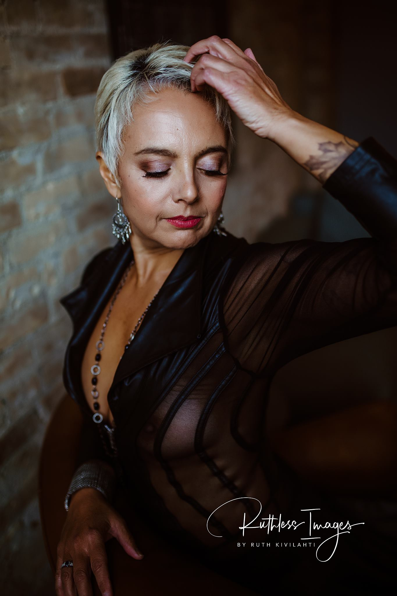 Image description: Tracy standing, looking downward, one hand brushing against the front of her short hair, with lipstick and eye shadow and really long eyelashes, dangling earrings, a long necklace, and a black long sleeved top with sheer bits and a plunging neckline. Exposed brick background.