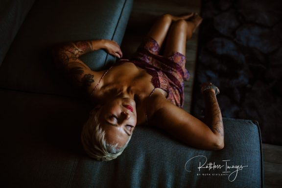 Image description: overhead shot of Tracy, sitting on the floor and leaning back into the corner of a sectional couch, in a sheer slip with lace edging and spaghetti straps, with her head back and tattooed arms on the couch.