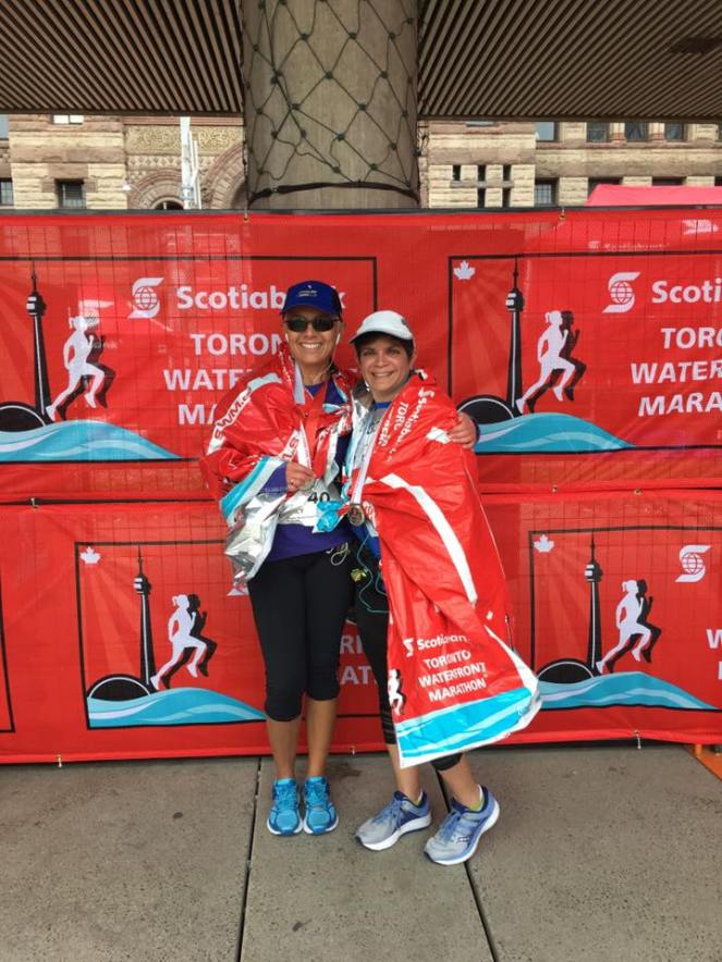 Image description: Tracy on left and Anita on right, both wrapped in foil blankets that say 'Scotiabank Toronto Waterfront Marathon', standing in front of a background that says the same.