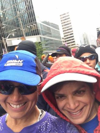 Image description: Tracy on left in ballcap and sunglasses, Anita on right in cap and hoodie, leaning in towards each other smiling, people and buildings in the background.