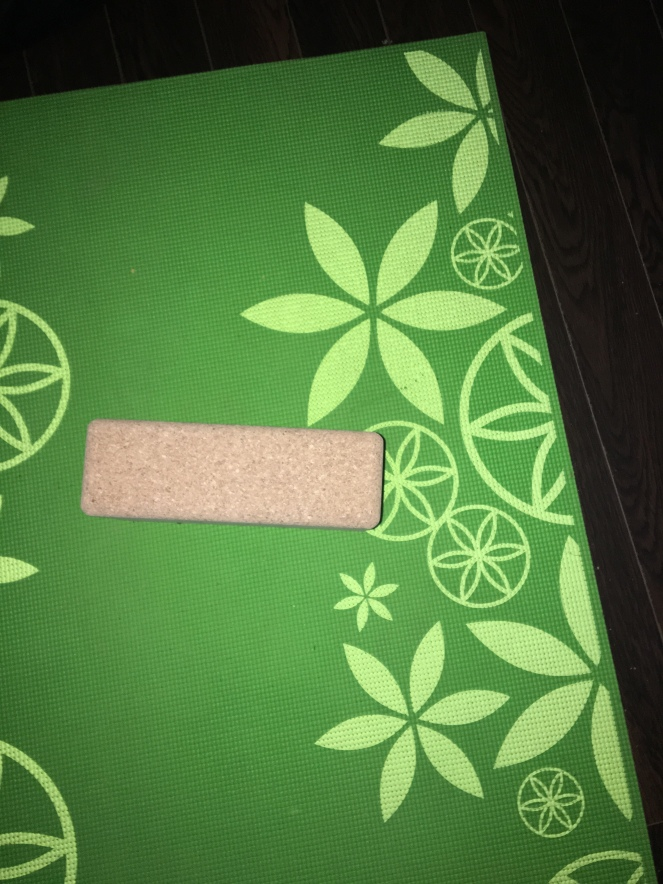 A rectangular, light brown cork yoga block sits atop a green yoga mat that is decorated with lighter green flowers. Dark brown floorboards are in the background.