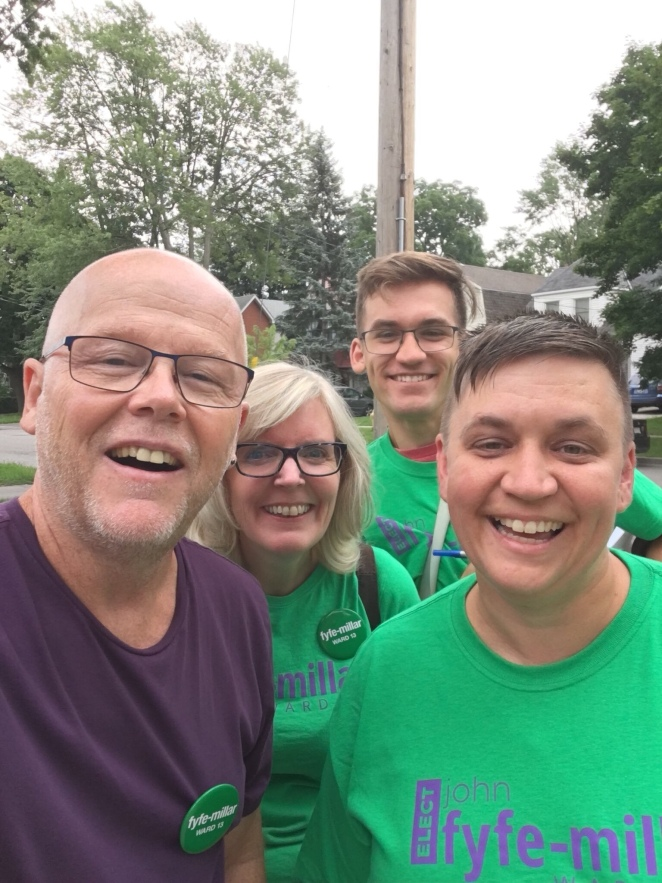 Four smiling humans wearing bright green t shirts standing on a sidewalk