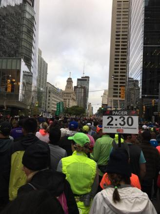 "Image description: the backs of crowd of people in running gear, tall buildings in the distance, and a sign that says ""PACER 2:30 Half Marathon Continuous."""