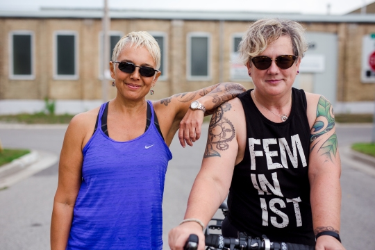 Image description: Street shot of Tracy (left) and Sam (right) from the waist up. Tracy is in a running tank, leaning on Sam's shoulder with her left elbow; Sam in on her bike, wearing a tank that says FEMINIST. Both are smiling, wearing sunglasses, street and building in background.